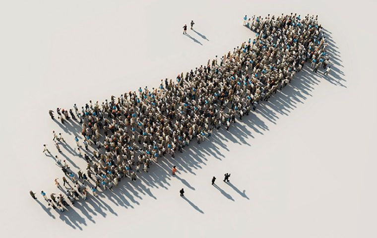 Crowd of people forming the shape of an upwards arrow