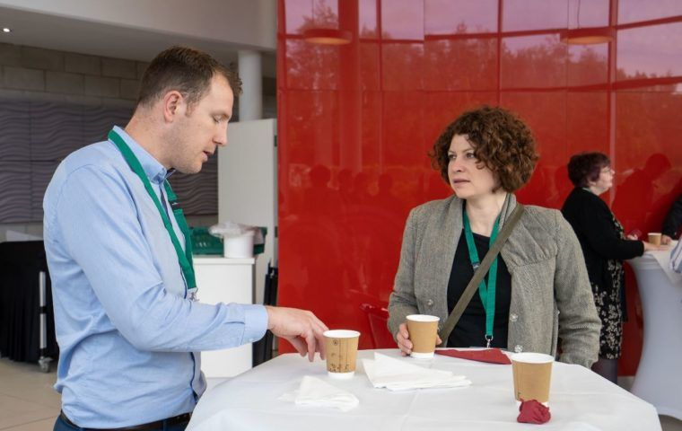 Two people talking over coffee at an event