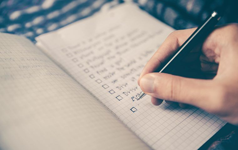 Image of a person writing a to do list into a notebook