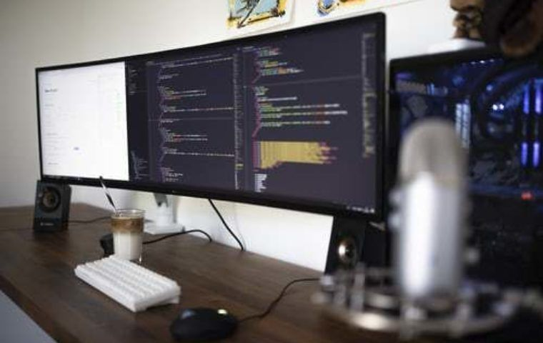 Image of three computer screens with coding on two of the screens