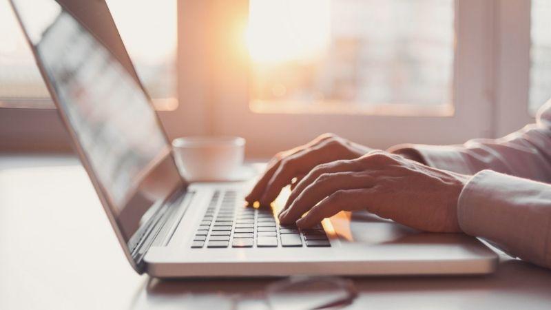 Image of man typing on a laptop