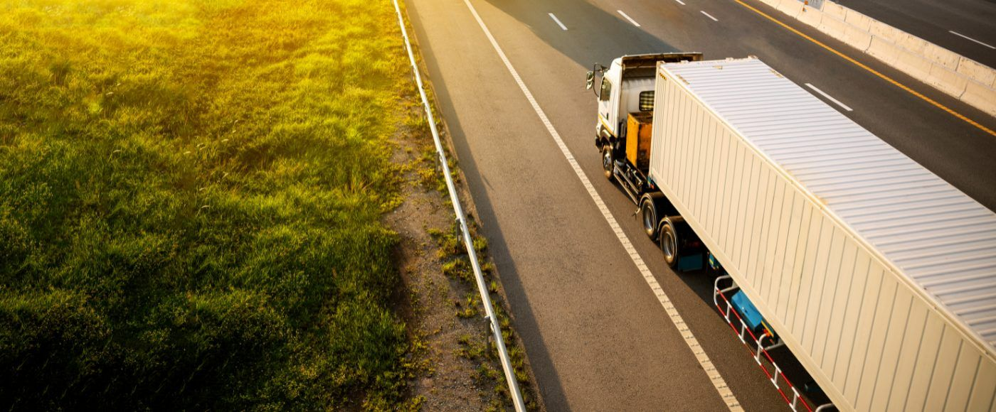 White lorry on a motorway with a container for trading goods.png
